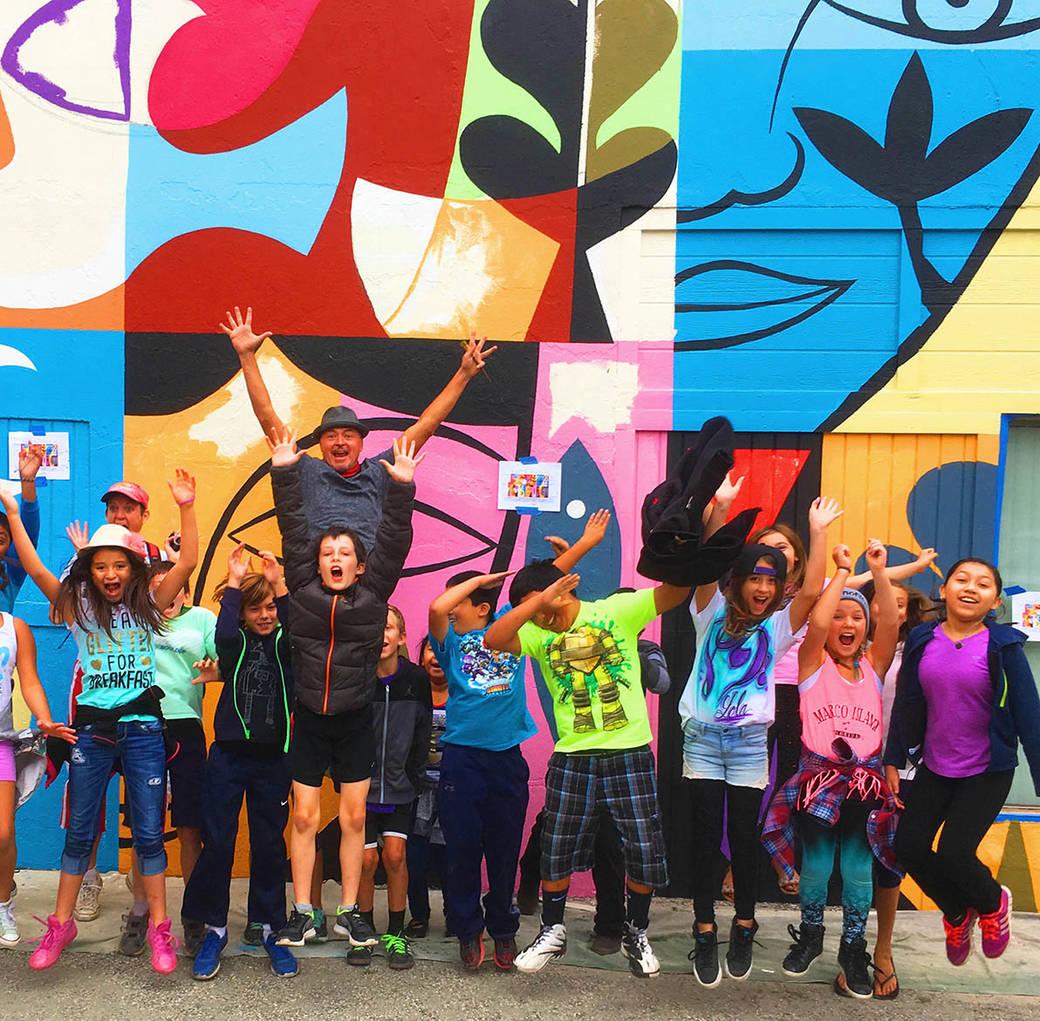 Rafael López jumping infront of a mural