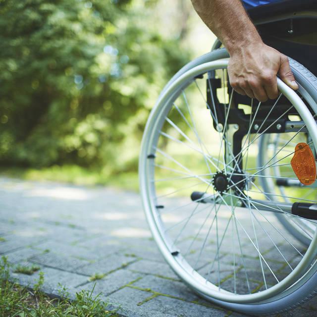 detail photo of a wheel chair wheel on a sidewalk