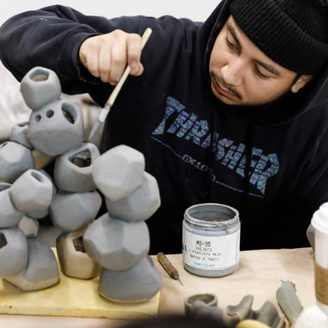 student painting ceramic piece