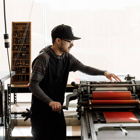 /Student working on vandercook press