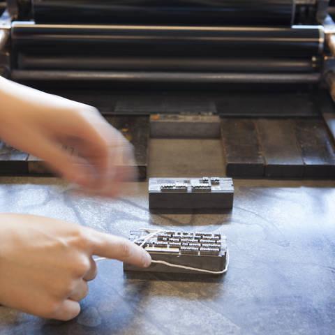 /hands placing letterpress type