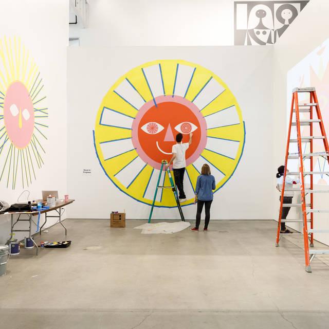 students painting stylized sun wall art