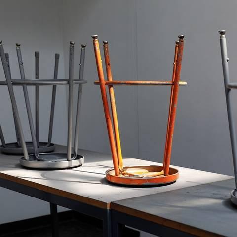 Orange stool upside-down on a desk