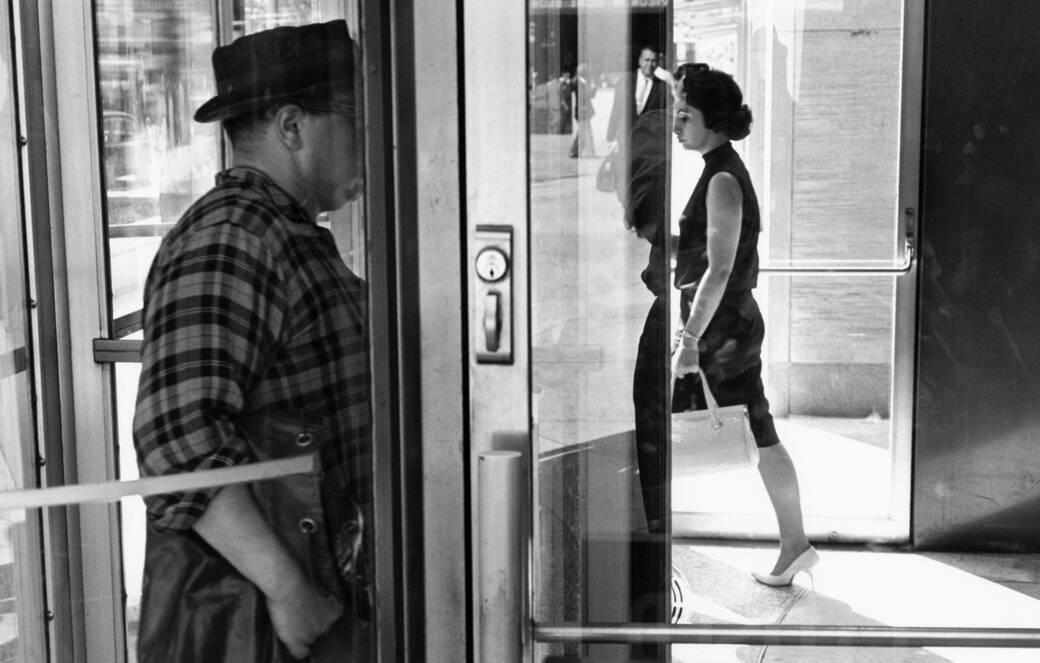 People walk through a revolving door in Lee Friedlander