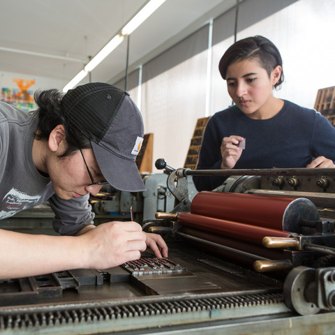 /students working on a vandercook letterpress printer
