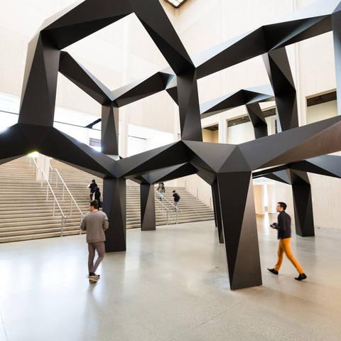 people walking under giant sculpture