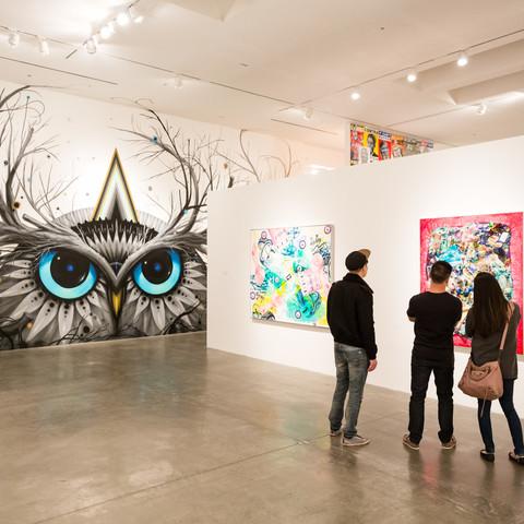 three people looking at art in gallery