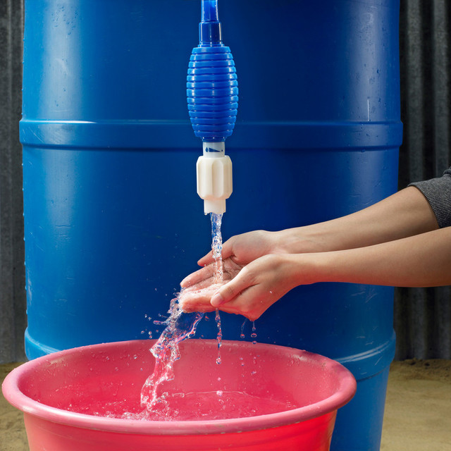 woman rinsing hands over bucket